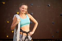 站立与在肩膀的绳索的运动服的活跃少妇对人为训练上升的墙壁 微笑的岩石 库存照片