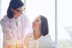 站立与在试验室工怍人员做的techer的年轻女性科学家 库存图片
