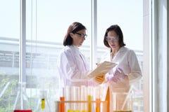 站立与在试验室工怍人员做的techer的年轻女性科学家 库存照片