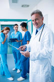 站立与在走廊的X-射线报告的微笑的医生画象 免版税库存照片