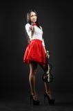 站立与在黑背景的一把小提琴的一个微笑的女孩 免版税库存图片