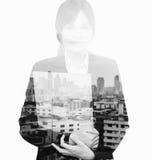 站立与城市的一个愉快的亚裔女商人的两次曝光画象在背景中 免版税图库摄影