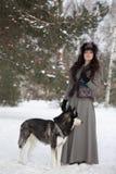 站立与多壳的狗的可爱的少妇 免版税库存图片