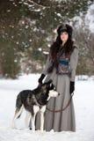 站立与多壳的狗的可爱的少妇 免版税图库摄影