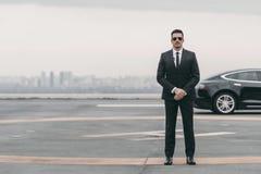 站立与太阳镜和安全听筒的严肃的保镖在停机坪和看 库存图片