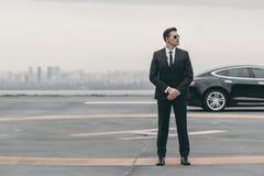 站立与太阳镜和安全听筒的严肃的保镖在停机坪和看 免版税库存照片