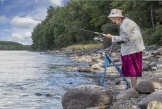 站立与她的步行者的一名资深妇女在湖和钓鱼旁边 免版税库存照片