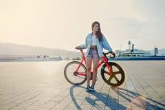 站立与她的现代桃红色自行车的年轻棕色毛发的妇女在日落 免版税库存图片