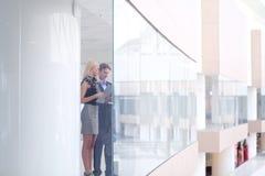 站立与她的职员的女商人在背景中在现代办公室 免版税库存图片