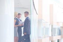 站立与她的职员的女商人在背景中在现代办公室 免版税图库摄影