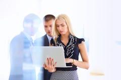站立与她的职员的女商人在背景中在现代办公室 库存照片