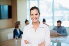 站立与她的胳膊的美丽的商业主管在办公室横渡了 图库摄影