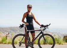 站立与她的自行车的确信的女性骑自行车者 免版税库存照片