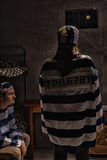 站立与她的ne的女囚犯佩带的监狱制服 免版税库存照片