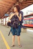站立与巨大的行李的美丽的旅游旅客 免版税库存图片