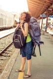 站立与巨大的行李的美丽的旅游旅客 免版税图库摄影