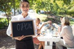 站立与开放标志板的微笑的女服务员 库存照片