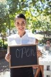 站立与开放标志板的微笑的女服务员 图库摄影
