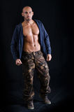 站立与开放运动衫和军用裤子的秃头年轻人 图库摄影