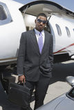 站立与态度的商人在机场 免版税库存照片