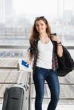 站立与手提箱和背包和持与票的太阳镜的深色头发的妇女一本护照 免版税库存图片