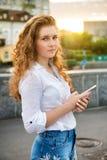 站立与手机的青少年的女孩户外 免版税库存照片