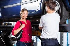 站立与技工的愉快的顾客在车库 免版税库存照片