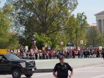 站立与抗议者的警察在背景中 免版税库存图片