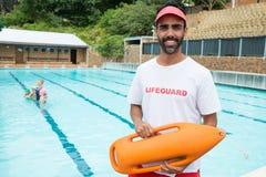 站立与抢救浮体的救生员在游泳池边附近 免版税图库摄影