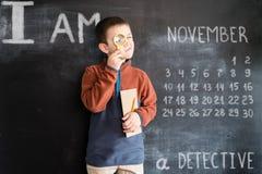 站立与放大镜和笔记本的年轻男孩` s在他的在黑板附近递 侦探年轻人 创造性的设计 免版税库存照片