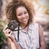 站立与数字照相机的愉快的妇女画象 库存照片