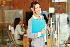 站立与文件夹的快乐的逗人喜爱的女实业家 免版税库存照片