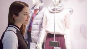 站立与时装模特的美丽的可爱的少妇近的窗口商店 女性看的窗口商店 影视素材