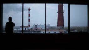 站立与智能手机的商人在窗口旁边在办公室反对天空 股票录像