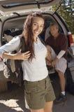 站立与朋友的画象妇女坐在汽车起动 免版税库存照片
