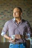 站立与杯子coffe和看窗口的信心印地安人 库存照片