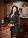 站立与杯的美丽的肉欲的妇女在红砖壁炉的酒 库存图片