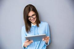 站立与桌计算机的愉快的女实业家 库存照片