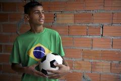 站立与橄榄球的年轻巴西足球运动员画象  库存照片