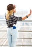 站立与火车站的一件镶边毛线衣和帽子的旅游白肤金发的女孩和做selfie 回到视图 免版税库存照片