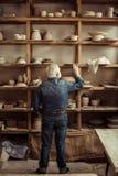 站立与瓦器物品的近的架子和搜寻某事的资深陶瓷工在车间 库存图片