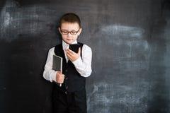 站立与电话和笔记本的年轻男孩` s在他的在黑板附近递 新生意人 2019加州的创造性的设计观念 免版税库存图片