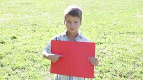 站立与空的空白的横幅的哀伤的男孩 股票视频