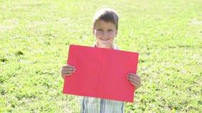 站立与空的空白的横幅的微笑的男孩 股票录像