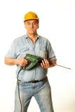 站立与穿孔器的一顶黄色安全帽的工作者 免版税图库摄影