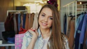 站立与纸袋在衣物商店和看照相机微笑的可爱的女孩特写镜头画象  股票录像