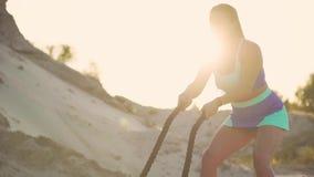 站立与绳索的含沙事业的美丽的女孩运动员做在阳光下站立在沙子的锻炼 股票录像