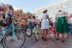 站立与老自行车的葡萄酒衣物的活跃妇女在欧洲 免版税图库摄影