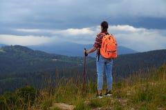 站立与背包和杆的Femake远足者在山 免版税库存照片