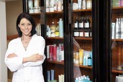 站立与胳膊横渡和化妆用品的美容院雇员的画象在背景中 库存图片